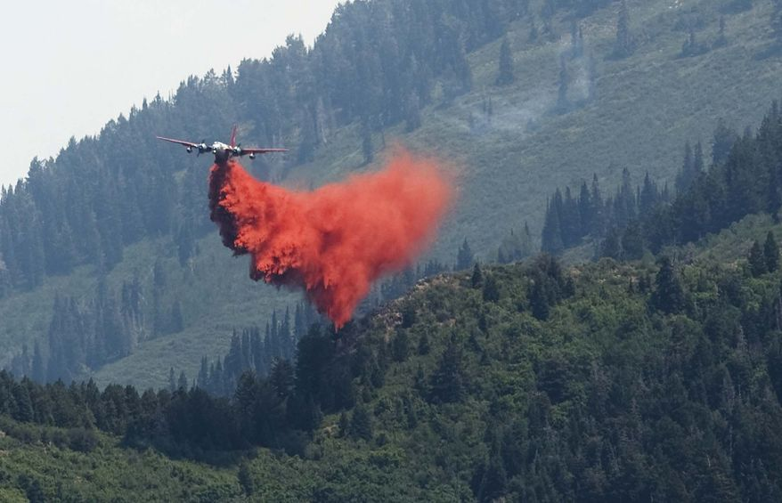 An air tanker filled with fire retardant makes a drop on the north end of the wildfire in Alpine, Utah, on Wednesday, July 4, 2012. (AP Photo/Salt Lake Tribune, Leah Hogsten)