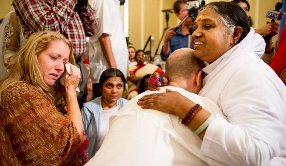 "Kimberly Taylor of Charlottesville, Va., left, cries as she watches spiritual leader Mata Amritanandamayi [cq], right, also known as ""Amma"" or the ""Hugging Saint"", receive David Ernest Wachter [cq], second from right, with a hug and blessing at the Hilton Alexandria Mark Center, Alexandria, Va., Friday, July 6, 2012. The spiritual leader is on a ten city tour through North America with the help of volunteers helping her throughout her visit. (Andrew Harnik/The Washington Times)"