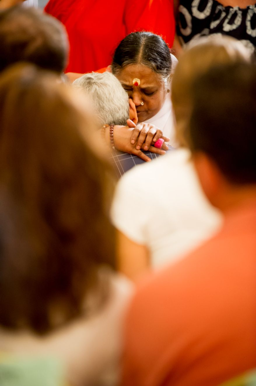 "Spiritual leader Mata Amritanandamayi, top center, also known as ""Amma"" or the ""Hugging Saint,"" receives a follower with a hug and blessing at the Hilton Alexandria Mark Center, Alexandria, Va., Friday, July 6, 2012. (Andrew Harnik/The Washington Times)"