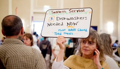 """Volunteer Kerry Fitzpatrick of Seattle, Wash. walks around with a sign asking for help washing dishes as spiritual leader Mata Amritanandamayi, also known as """"Amma"""" or the """"Hugging Saint,"""" hugs and blesses followers at the Hilton Alexandria Mark Center, Alexandria, Va., Friday, July 6, 2012. (Andrew Harnik/The Washington Times)"""