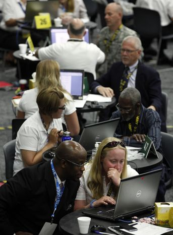 **FILE** Tressa Miller (right) helps military veteran Roger Porter, of Detroit, with resume career counseling in Detroit on June 26, 2012. (Associated Press)