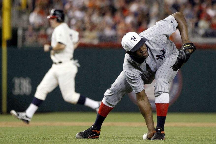 San Francisco Giants relief pitcher Santiago Casilla, right, cannot field a ground ball as Washington Nationals' Tyler Moore runs to third base during the ninth inning of a baseball game, Thursday, July 5, 2012, in Washington. The Nationals won 6-5. (AP Photo/Evan Vucci)