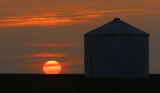 The sun sets in Pleasant Plains, Ill., on July 5, 2012. Corn and soybean crops are struggling under dry conditions and a record-breaking heat wave that is over most of the country. (Associated Press)