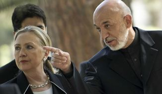 U.S. Secretary of State Hillary Rodham Clinton, left, walks with President of Afghanistan Hamid Karzai to a press conference at the Presidential Palace in Kabul, Saturday, July 7, 2012. (AP Photo/Brendan Smialowski, Pool)