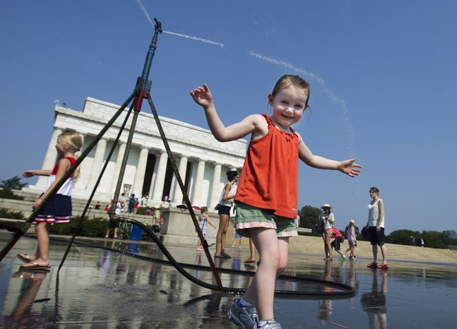 Sophie, 3, from Connecticut, frolics with a water sprinkler set up at the National Mall near the Lincoln Memorial, rear, in Washington Saturday, July 7, 2012.  The heat gripping much of the country is set to peak Saturday in many places, including some Northeast cities, where temperatures close to or surpassing 100 degrees are expected. (AP Photo/Manuel Balce Ceneta)