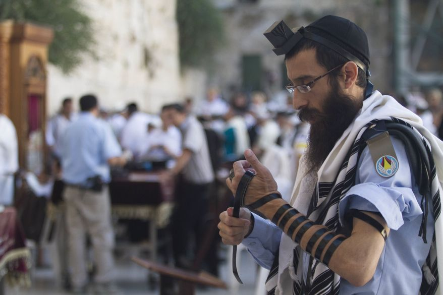 ** FILE ** In this Monday, July 2, 2012, an Israeli soldier prays next to the Western Wall, the holiest site where Jews can pray, in Jerusalem's Old City. (AP Photo/Dan Balilty)
