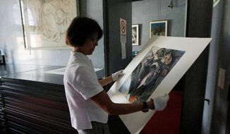 "Francesca Rossi, curator in charge of the Sforzesco Castle drawings collection, examines a work by Umberto Boccioni in the same room where Simone Peterzano sketches are preserved. She says art historians who claim to have found early drawings of Caravaggio, a student of Peterzano, are naive and ""never came here in the drawings department to scrutinize the works."" Yet Maurizio Bernardelli Curuz says he was able to visit the collection after hours and ""saw the originals."" (Associated Press)"