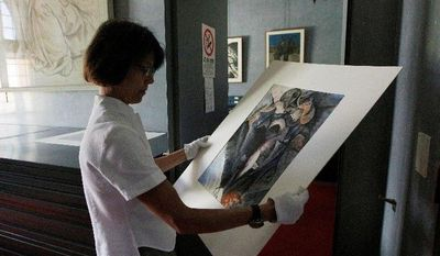 """Francesca Rossi, curator in charge of the Sforzesco Castle drawings collection, examines a work by Umberto Boccioni in the same room where Simone Peterzano sketches are preserved. She says art historians who claim to have found early drawings of Caravaggio, a student of Peterzano, are naive and """"never came here in the drawings department to scrutinize the works."""" Yet Maurizio Bernardelli Curuz says he was able to visit the collection after hours and """"saw the originals."""" (Associated Press)"""