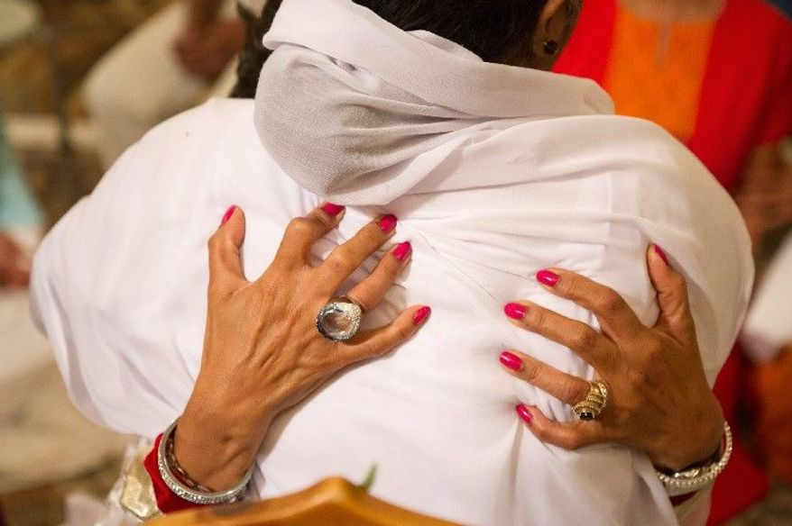 """The woman known as the """"hugging saint"""" hugs and blesses Nilima Mehra, a producer with Global Television Network. (Andrew Harnik/The Washington Times)"""