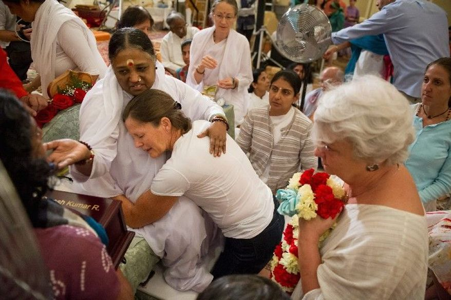 Spiritual leader Mata Amritanandamayi (left) hugs and blesses Sue Jones of Virginia Beach, Va., as Mildred Donlon (second from right) waits to be received at the Hilton Alexandria Mark Center in Alexandria on Friday. The spiritual leader from India is on a 10-city tour through North America. (Andrew Harnik/The Washington Times)