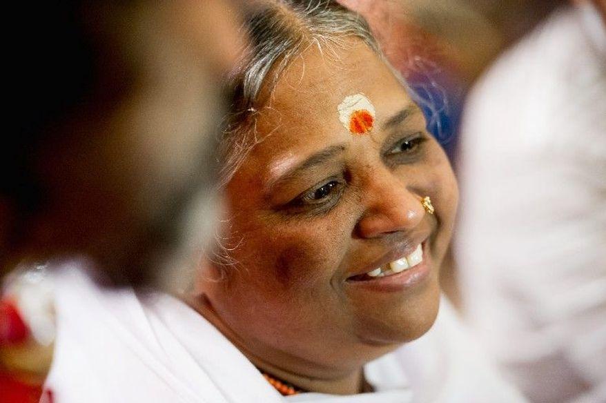 """Followers wait in a seated line holding numbered tokens to be redeemed for personal blessings from spiritual leader Mata Amritanandamayi at the Hilton Alexandria Mark Center on Friday. The woman known as the """"hugging saint"""" smiles as a steady stream of visitors approach her. (Andrew Harnik/The Washington Times)"""