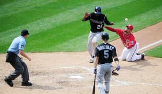 Dexter Fowler scores on a wild pitch by Washington reliever Michael Gonzalez (right) to tie the game 3-3 in the eighth inning. Colorado won 4-3 to take two of three games in the weeked series at Nationals Park. (Ryan M.L. Young/The Washington Times)