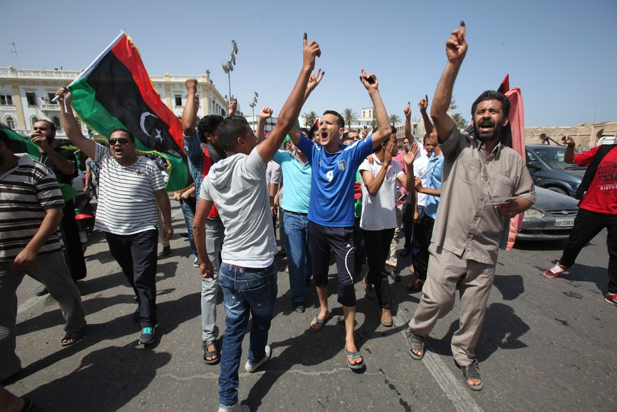 Libyans celebrate July 7, 2012, in Martyrs' Square in Tripoli, Libya, by holding up ink-marked fingers, showing they have voted in the first parliamentary election after last year's overthrow and killing of longtime leader Moammar Gadhafi. (Associated Press)