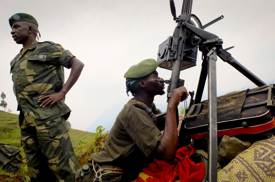 Soldiers from the M23 rebel group show off July 7, 2012, in Bunagana, Congo, weapons captured from government troops, who fled to neighboring Uganda a day earlier as the rebel group took control of the border town. (Associated Press)