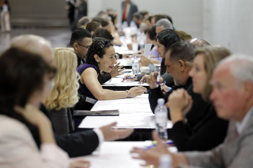 ** FILE ** In this June 13, 2012, file photo, job seekers have their resumes reviewed at a job fair expo in Anaheim, Calif. (AP Photo/Jae C. Hong, File)