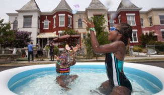 Nia Bailey (left), 8, of Washington, and Amari Swint, 8, of Philadelphia, throw water balloons while in an inflatable pool July 7, 2012, during a block party northwest Washington, D.C., during record heat with temperatures in the triple digits. (Associated Press)
