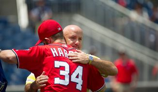 Nationals General Manager Executive Vice President of Baseball Operations Mike Rizzo gives a hug to Bryce Harper (34) prior to the game as the Washington Nationals host the Colorado Rockies. (Rod Lamkey Jr./The Washington Times)