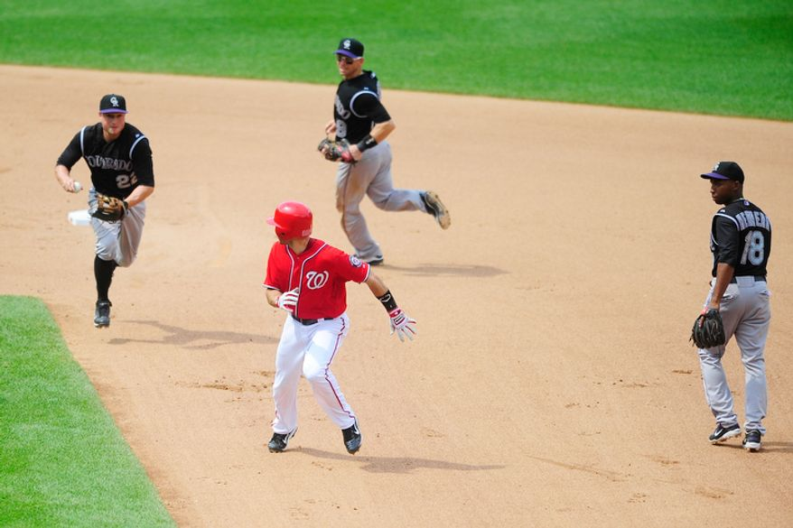 Steve Lombardozzi is swarmed by Rockies players while caught in a pickle.  (Ryan M.L. Young/The Washington Times)