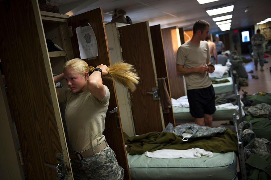 Sapper candidate and Army Captain Aston Armstrong brushes her hair  as she wakes up alongside the men after spending her first night in an actual bed after two grueling weeks in the field, a day after Sapper School training ended for the candidates at U.S. Army Maneuver Support Center (MANSCEN) and Fort Leonard Wood in Fort Leonard Wood, Mo., Thursday, June 28, 2012. (Rod Lamkey Jr./The Washington Times)
