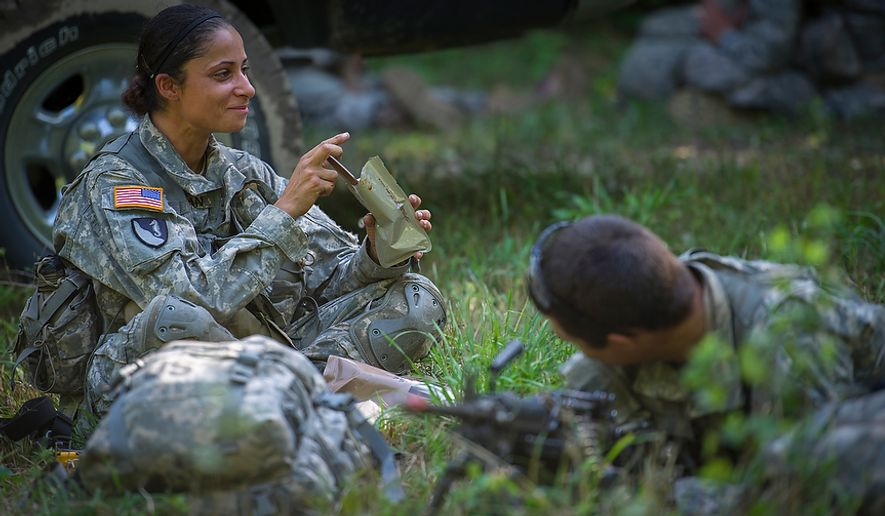 "Sapper candidate and Army Captain Stephanie Godman (left) takes her turn at lunch as she eats a military Meal Ready to Eat (MRE) while her ""Battle Buddy"" Sapper candidate and National Guard Staff Sargent Anthony Hughes keeps watch and is posted up in a clearing to help form a perimeter as the platoon breaks for a meal during another day of Sapper School training at U.S. Army Maneuver Support Center (MANSCEN) and Fort Leonard Wood in Fort Leonard Wood, Mo., Tuesday, June 26, 2012. (Rod Lamkey Jr./The Washington Times)"