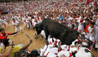 ** FILE ** A bull jumps over revelers July 8, 2012, in a bullring during the second running of the bulls at the San Fermin fiestas in Pamplona, Spain. (Associated Press)