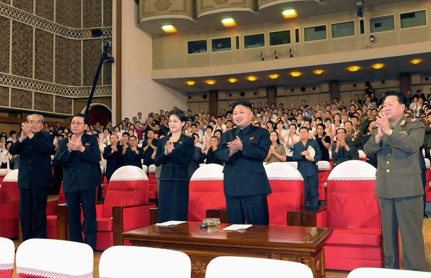 North Korean leader Kim Jong-un (center right) and others clap as they watch a performance in Pyongyang on Friday that featured Disney characters. (Korea News Service via Associated Press)