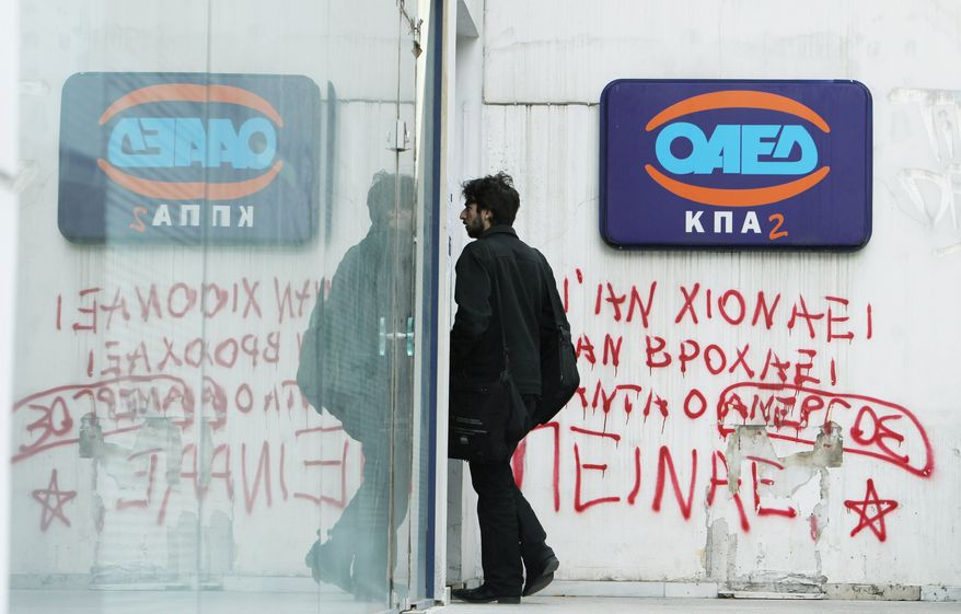 """A young man enters an office of the Labor Force Employment Organization, with graffiti under the logo of OAED reading ''Snow or rain the jobless are always hungry'' in Athens. Economists fear that years of unemployment could produce a European version of Japan's """"Lost Generation,"""" the young jobless adults of the 1990s. (Associated Press)"""