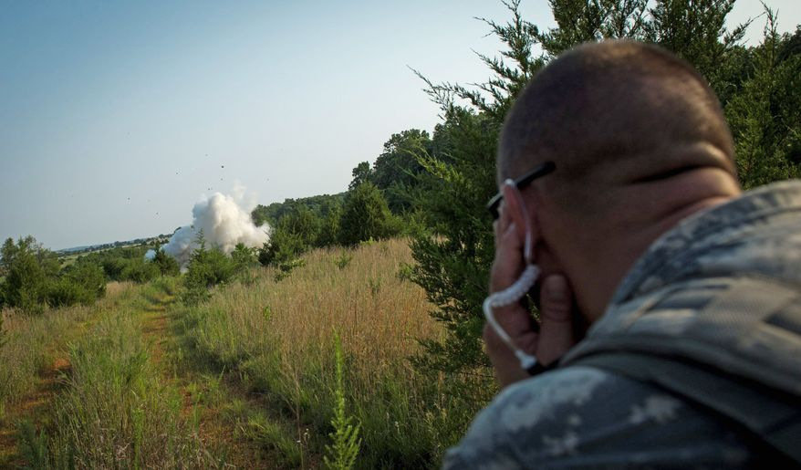 Army Sgt. 1st Class Steven Jaynes holds his ears as an explosive goes off during a mission. Only the top combat engineers and soldiers from a unit are chosen to attend the Sapper Leader Course at Fort Leonard Wood, Mo. (Rod Lamkey Jr./The Washington Times)