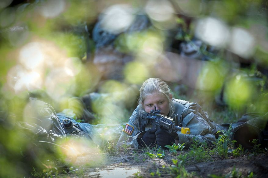 Army Capt. Aston Armstrong is posted in a clearing to help guard a perimeter as the platoon breaks for a meal during a training mission. The Massachusetts native graduated from the U.S. Military Academy in 2008 and sought to earn a coveted sapper badge. (Rod Lamkey Jr./The Washington Times)