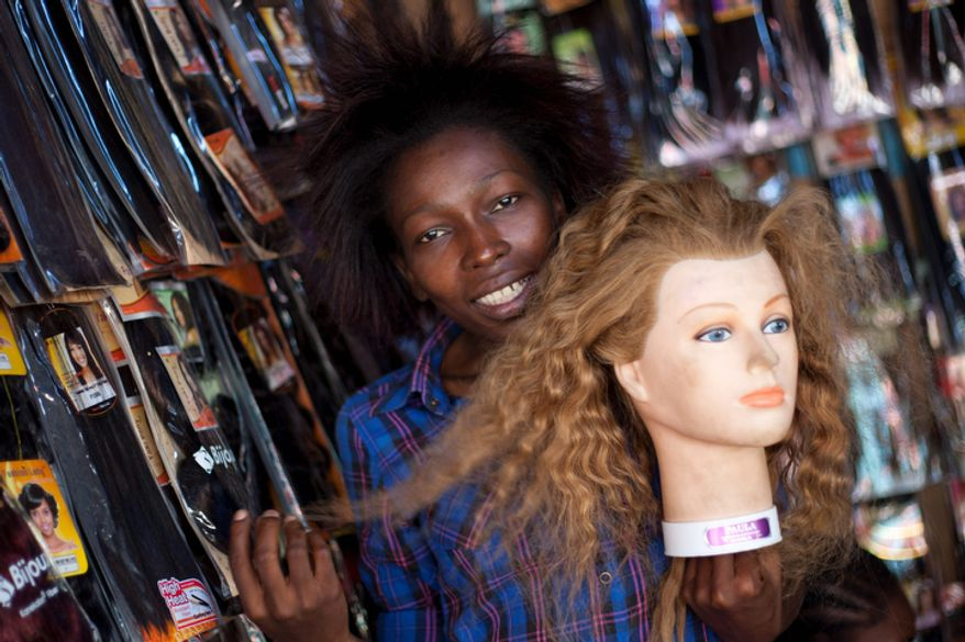 Hairdresser Cigarre Wanuese 28, poses for pictures as she holds a mannequin head at a hairpieces shop on a street in downtown Port-au-Prince, Haiti.  (AP Photo/Dieu Nalio Chery)