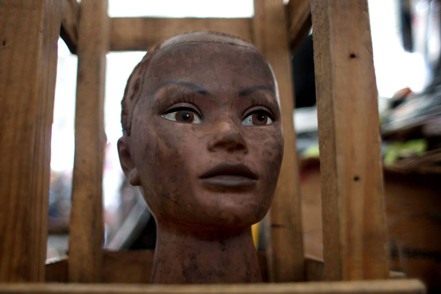 A mannequin head is displayed at a street stall in downtown Port-au-Prince, Haiti. After Haiti's devastating January 2010 earthquake, dozens of independent hair stylists that braided and colored hair in the capital's Iron Market moved their activities to the streets, where they resumed their businesses not long after the disaster. (AP Photo/Dieu Nalio Chery)