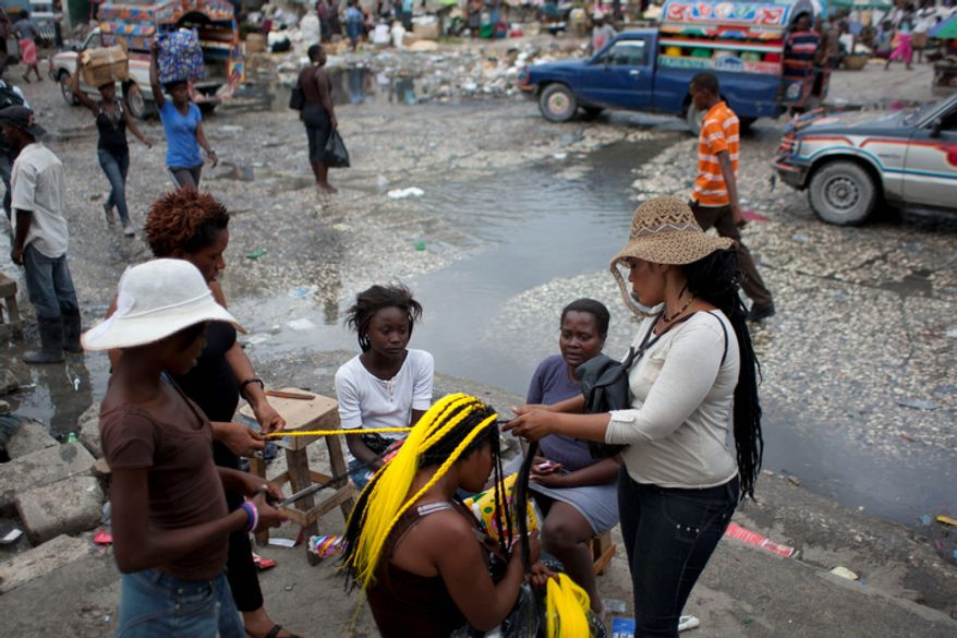 Hairdressers work on the hair of a client on a street in downtown Port-au-Prince, Haiti.  (AP Photo/Dieu Nalio Chery)