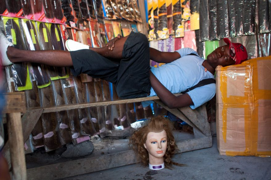 Anderson Pierre, 22, lies next to a mannequin head at his hairpieces shop on a street in downtown Port-au-Prince, Haiti.  (AP Photo/Dieu Nalio Chery)