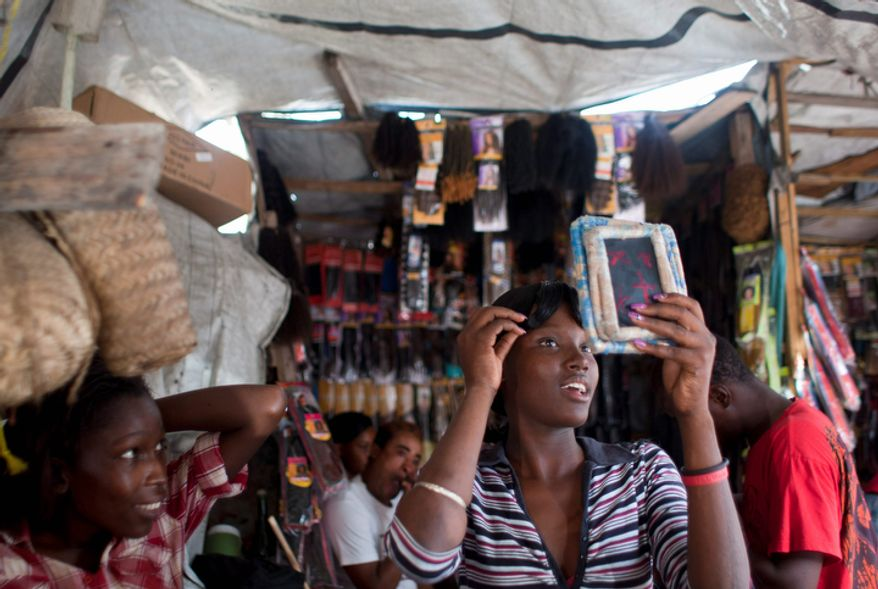 A client looks at herself on a mirror after having her hair combed at a street stall in downtown Port-au-Prince, Haiti. Before Haiti's devastating January 2010 earthquake dozens of independent hair stylists braided and colored hair in the capital's Iron Market, the commercial hub of downtown Port-au-Prince. The earthquake damaged the landmark Iron Market and the hairstylists moved their activities to the streets, where they resumed their businesses not long after the disaster. (AP Photo/Dieu Nalio Chery)