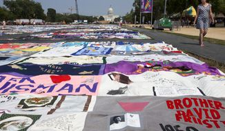 **FILE** People visit the AIDS Memorial Quilt on display as part of the Smithsonian Folklife Festival on the National Mall in Washington on July 5, 2012. (Associated Press)