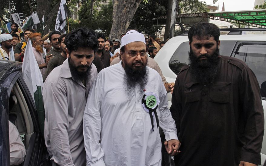 ** FILE ** Hafiz Saeed (center), leader of Pakistani religious group Jamaat-ud-Dawa, is surrounded by guards as he arrives July 8, 2012, in Lahore, Pakistan, to attend a rally condemning the movement of NATO supplies to Afghanistan through Pakistan. (Associated Press)