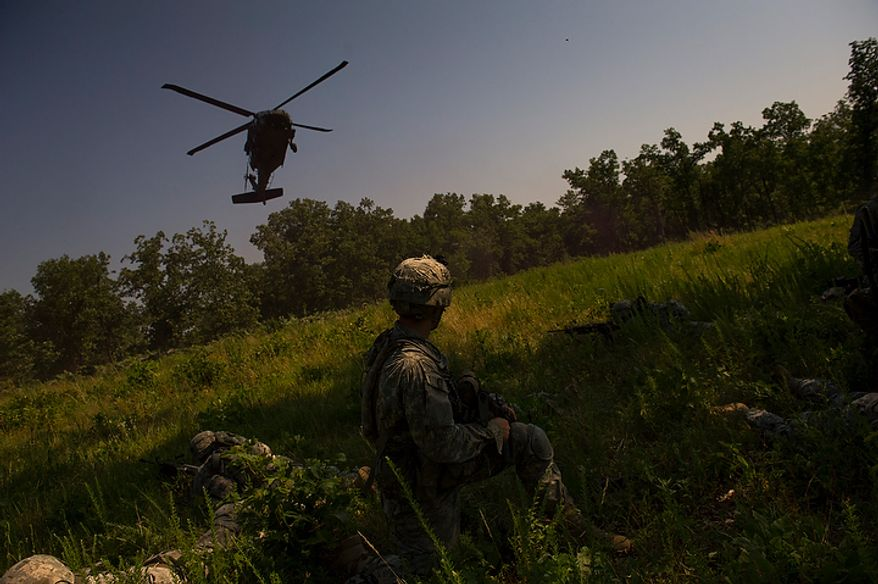 The platoon of Sapper candidates lie low in the grass as they watch their Black Hawk helicopter ride arrive to transport them to a base for the planning of a mission, during another day of Sapper School training at U.S. Army Maneuver Support Center (MANSCEN) and Fort Leonard Wood in Fort Leonard Wood, Mo., Wednesday, June 27, 2012. (Rod Lamkey Jr./The Washington Times)