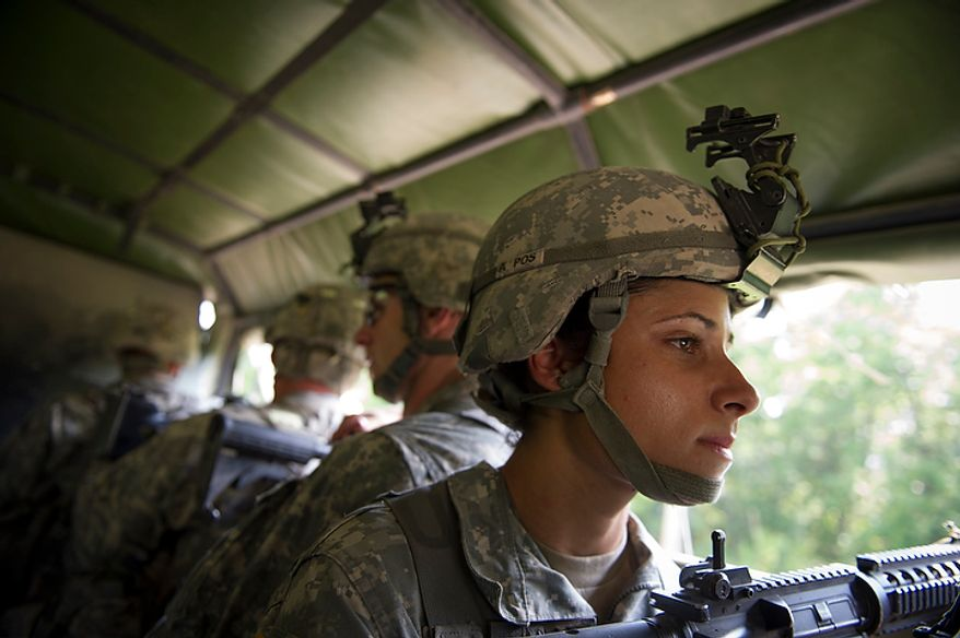 With her weapon pointed outward from the truck, Sapper candidate and Army Captain Stephanie Godman watches for a possible ambush while riding in the sweltering heat with some members of the platoon aboard a truck to be transported to a site for the next mission during another day of Sapper School training at U.S. Army Maneuver Support Center (MANSCEN) and Fort Leonard Wood in Fort Leonard Wood, Mo., Monday, June 25, 2012. (Rod Lamkey Jr./The Washington Times)