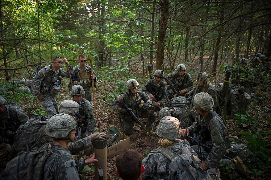 Taking the leadership role today, Sapper candidate and Army Captain Aston Armstrong talks in whispers to her platoon for the next mission to detonate explosives, during another day of Sapper School training at U.S. Army Maneuver Support Center (MANSCEN) and Fort Leonard Wood in Fort Leonard Wood, Mo., Monday, June 25, 2012. (Rod Lamkey Jr./The Washington Times)