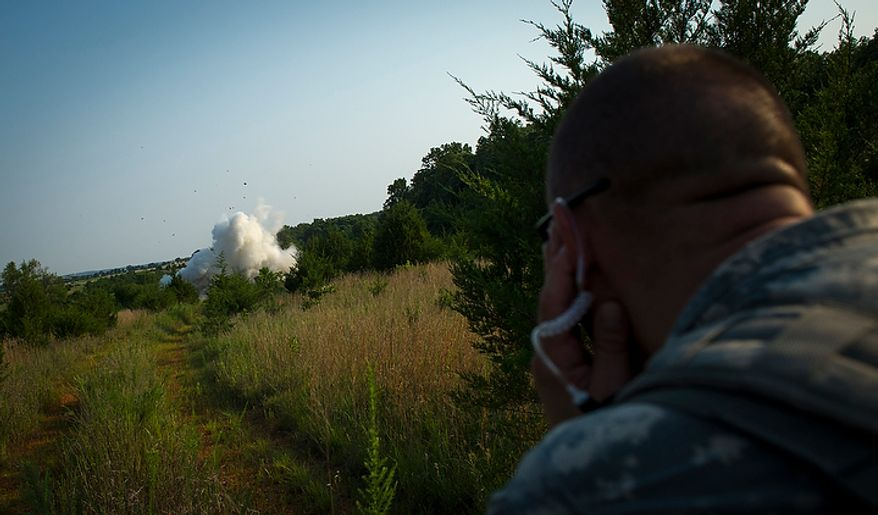 Army SFC Steven Jaynes holds his ears during an explosion for a mission, during another day of Sapper School training at U.S. Army Maneuver Support Center (MANSCEN) and Fort Leonard Wood in Fort Leonard Wood, Mo., Monday, June 25, 2012. (Rod Lamkey Jr./The Washington Times)