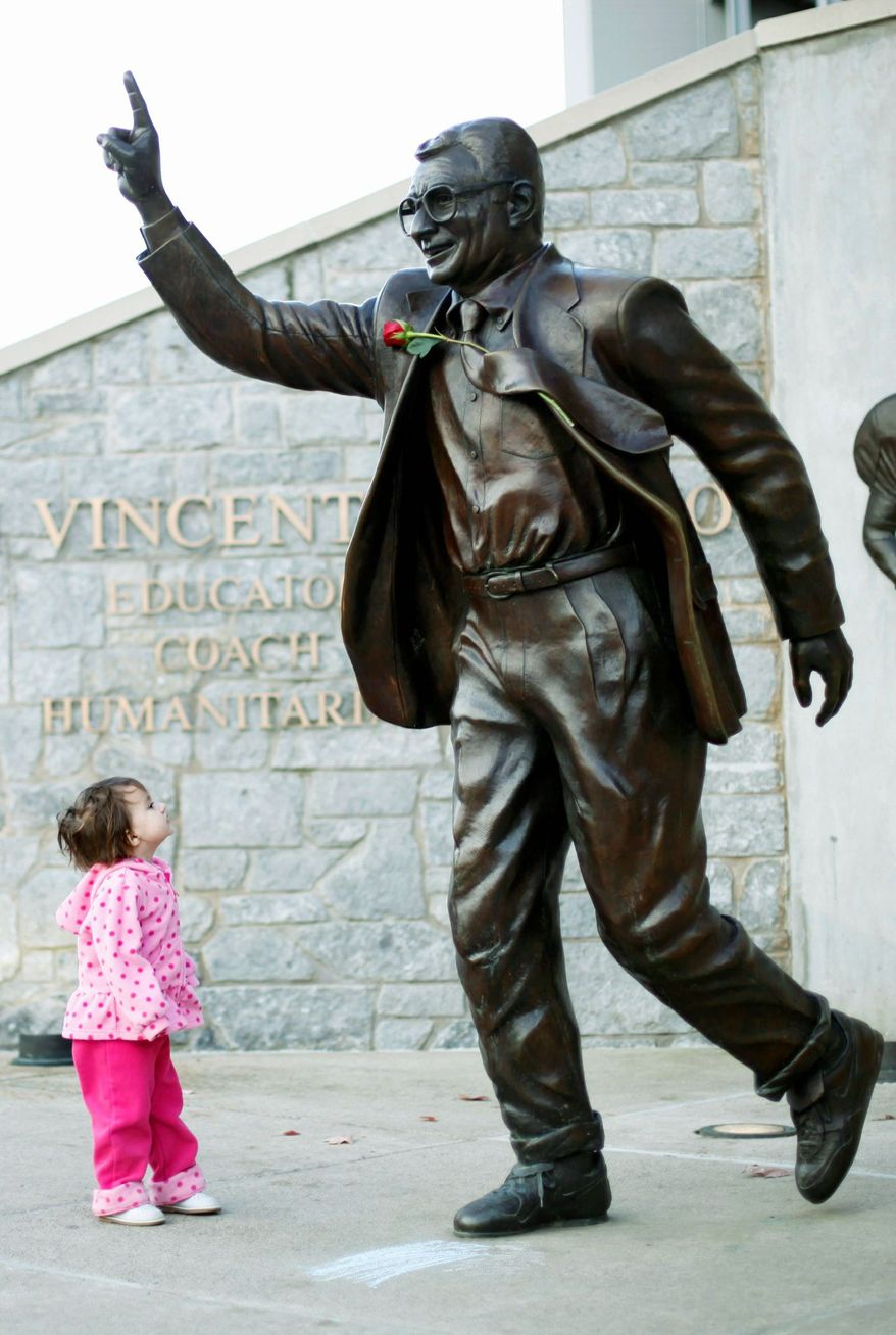 **FILE** Sabine Briggs, 2, looks up at a statue of Joe Paterno outside Beaver Stadium on Penn State's campus on Nov. 11, 2011. (Associated Press)