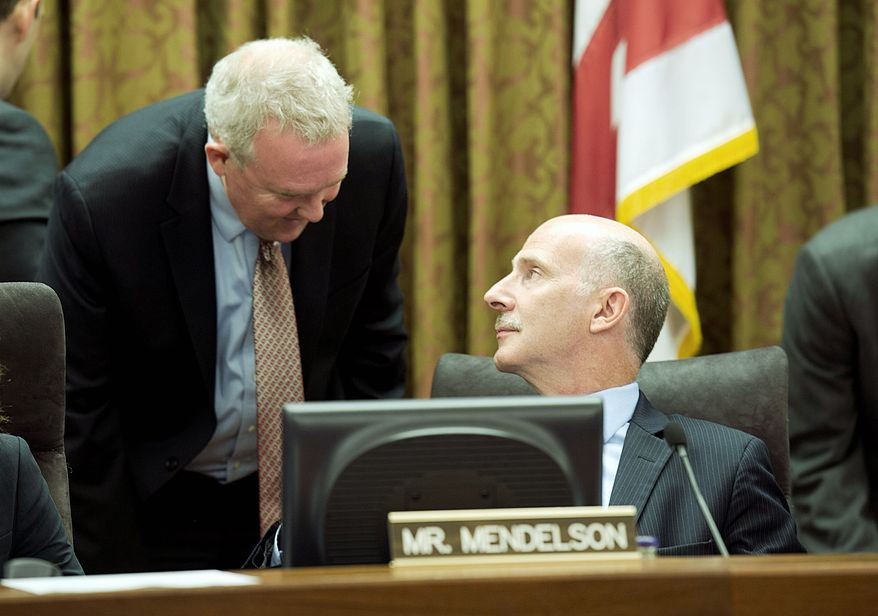 D.C. Council member Tommy Wells (left) talks with acting Chairman Phil Mendelson. (Barbara L. Salisbury/The Washington Times)