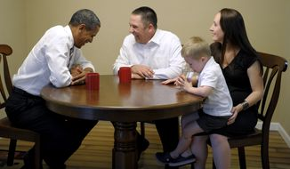 President Obama shares a laugh July 10, 2012, with Jason and Ali McLaughlin and their son, Cooper, while visiting their home in Cedar Rapids, Iowa. (Associated Press)