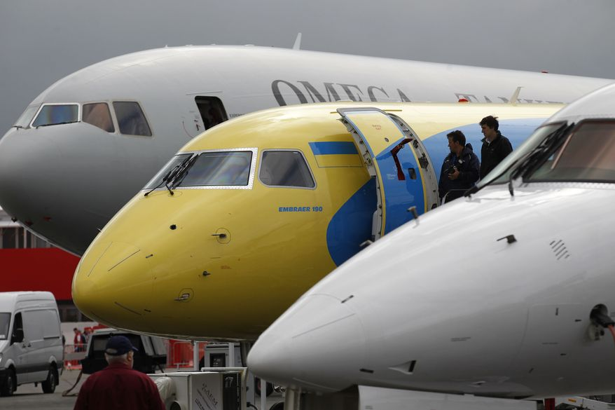 Visitors check out an aircraft on display at the Farnborough International Airshow in Farnborough, England, on Monday, July 9, 2012. (AP Photo/Sang Tan)