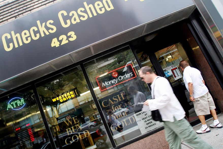 A passer-by looks at the business hours of a check-cashing store in the Hell's Kitchen neighborhood of Manhattan in New York City. A bill in the House would exempt such outlets, as well as pawnshops and payday-lending places from oversight by a new federal consumer finance watchdog agency. (Associated Press)
