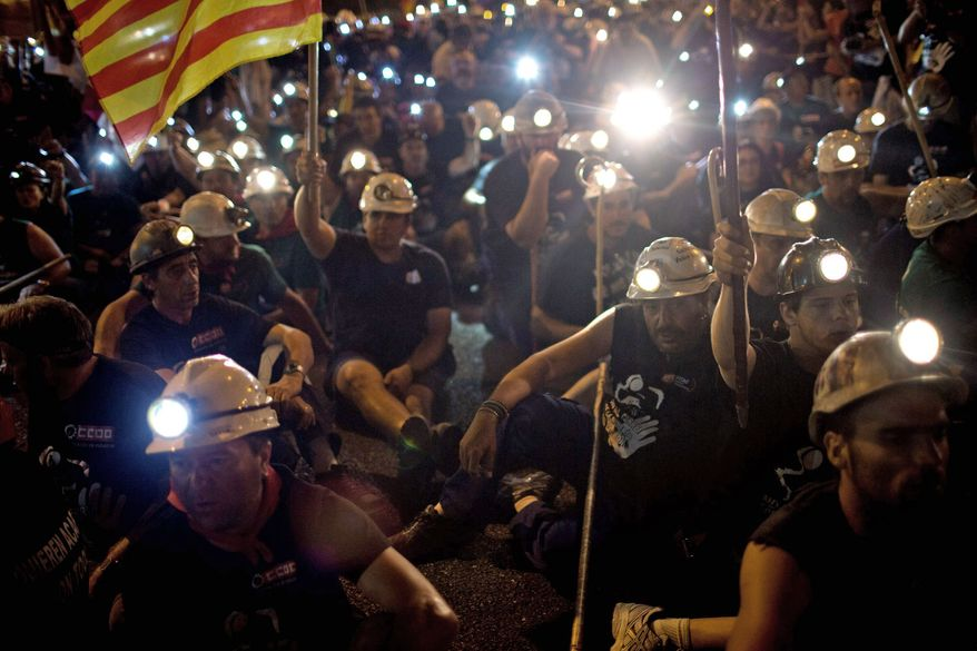 Miners rest during their march on Tuesday, illuminating the night with the lights on their work helmets. They were on their way to Madrid to protest cuts in the subsidy the government provides them. (Associated Press)