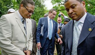 D.C. Mayor Vincent C. Gray is surrounded as he answers reporters' questions about campaign operative Jeanne C. Harris who pleaded guilty Tuesday to funneling undocumented campaign funds to his campaign. (Andrew Harnik/The Washington Times)