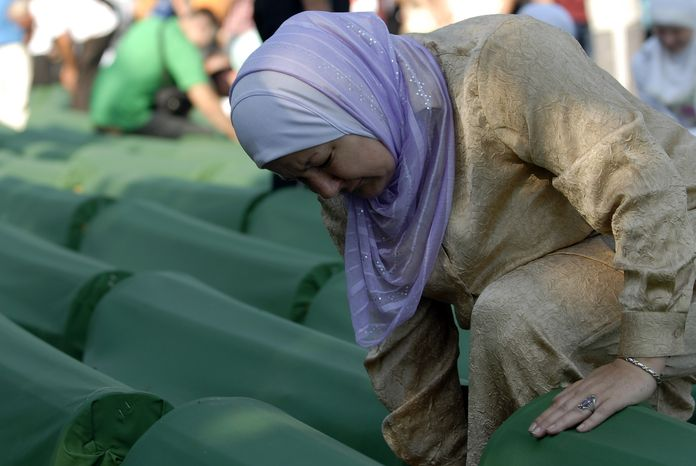A Bosnian Muslim woman weeps as she touches the coffin of a relative among the more than 500 caskets displayed at the Potocari Memorial Cemetery near Srebrenica, Bosnia-Herzegovina, on Wednesday, July 11, 2012. (AP Photo/Sulejman Omerbasic)