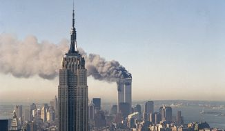 "*"" FILE ** The twin towers of the World Trade Center burn on Sept. 11, 2001, behind the Empire State Building in New York. (Associated Press)"