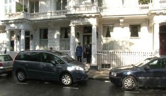 This photo taken from PA video shows police outside a house in Cadogan Place, Chelsea, after the body of Eva Rausing, a member of the family behind the Tetra-Pak drinks carton empire and one of the richest women in Britain was found, Tuesday July 10, 2012. (AP Photo/PA Video, Leanne Rinne)